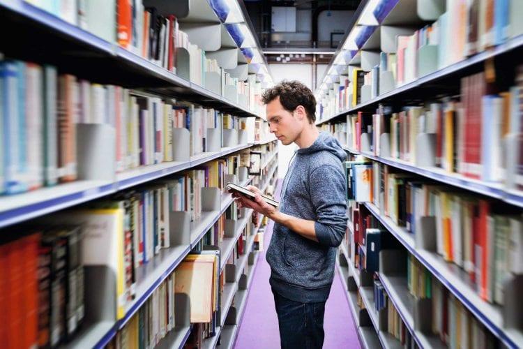 Mann liest im Gang einer Bibliothek