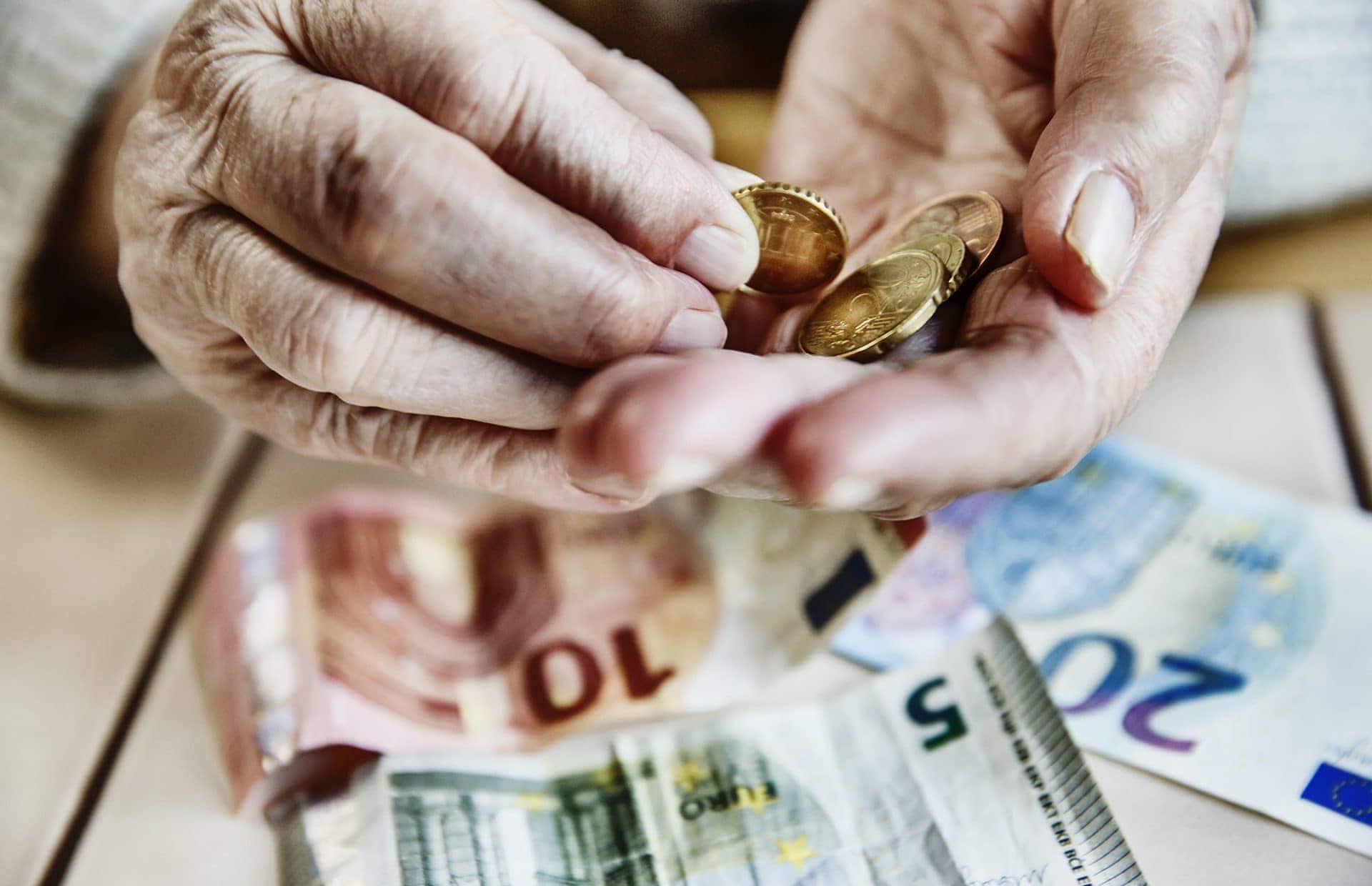Hände eines alten Menschen mit Centmünzen und kleinen Geldscheinen