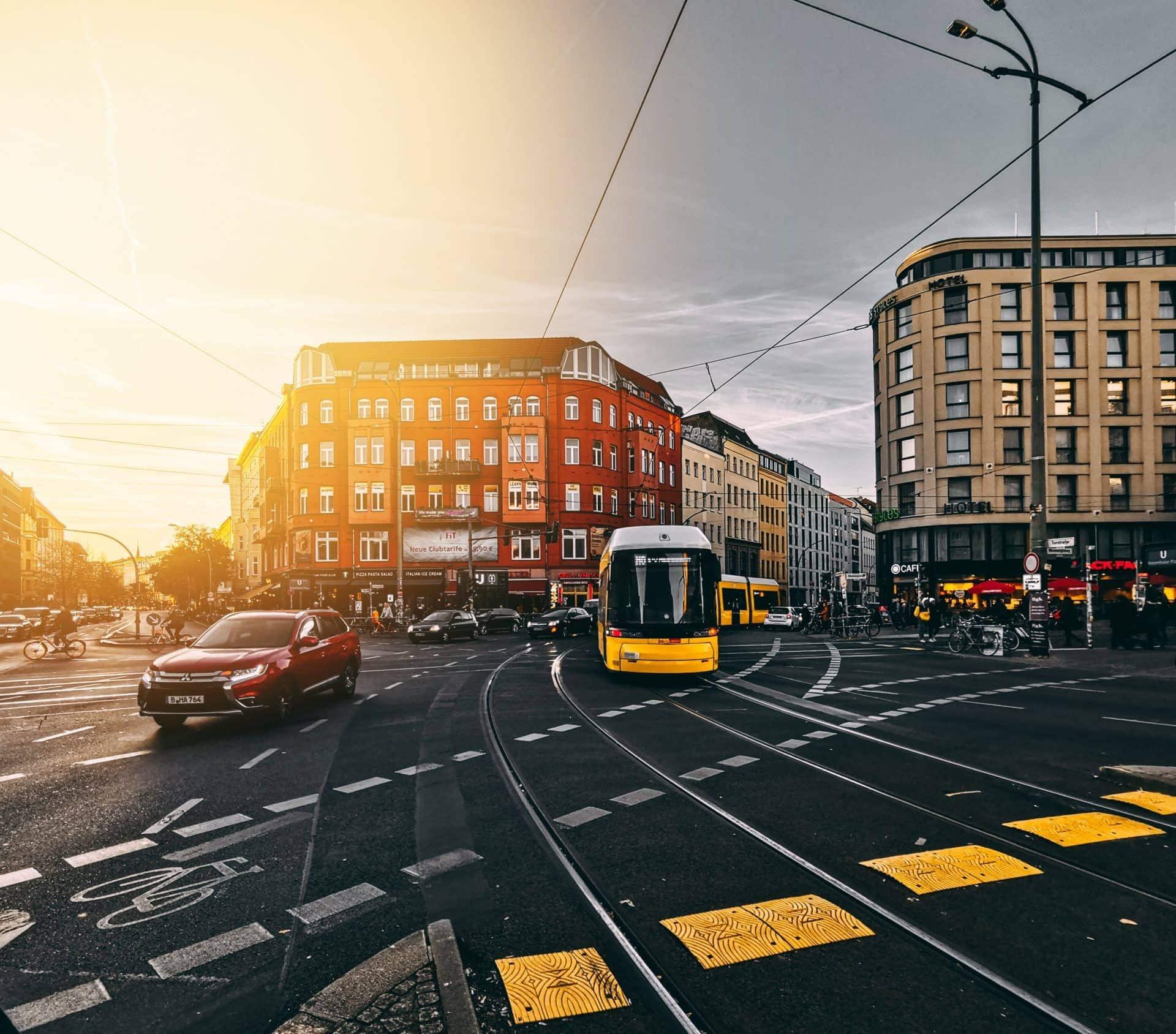Straßenbahn fährt im Sonnenuntergang über Kreuzung in Berlin