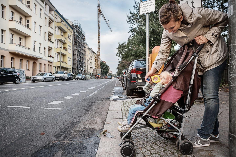 Mutter mit Kind im Buggy am Straßenrand