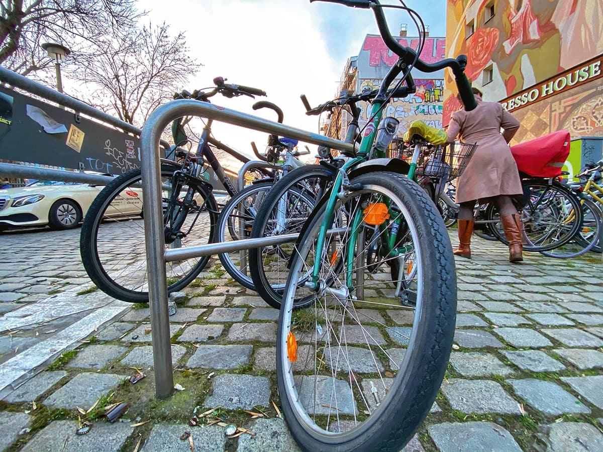 Fahrräder, Fußgängerin & Autos auf den Straßen Berlins.