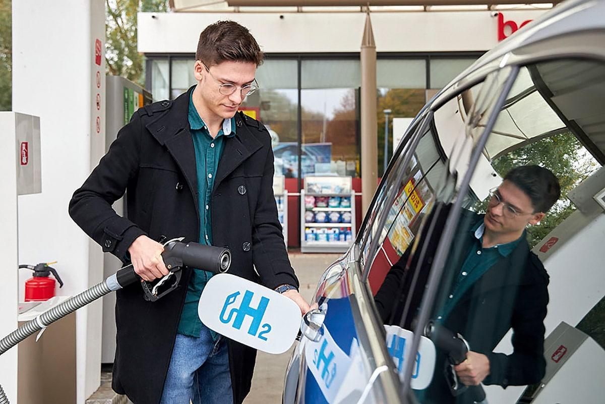 Ein Mann tankt Wasserstoff an einer Tankstelle.