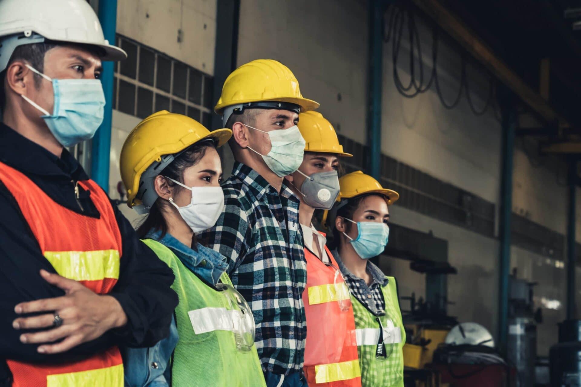 Arbeiterinnen und Arbeiter mit Mund-Nase-Maske