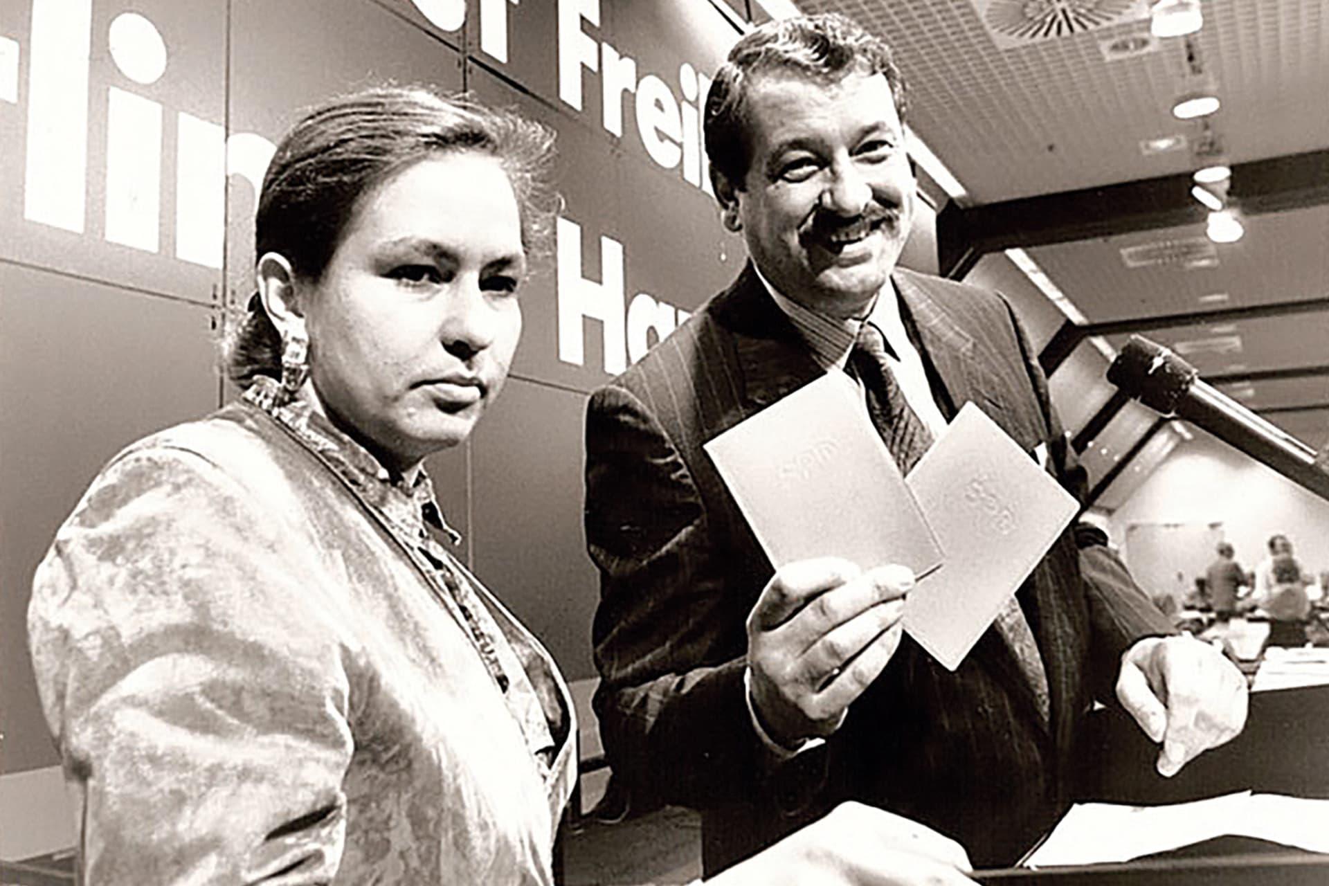 Anne-Kathrin Pauk (l.), bis zu diesem Zeitpunkt Vorsitzende des SPD-Bezirksverbandes Ost-Berlin, erhält nach dem Zusammenschluss mit dem West-Berliner SPD-Landesverband, als erste ihr Parteibuch aus der Hand von Hans-Georg Lorenz, damals Geschäftsführender Landesvorsitzender.