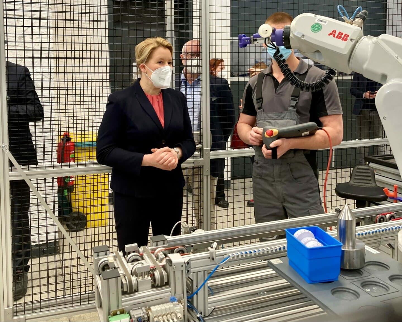 Franziska Giffey lässt sich von einem Auszubildenden im ABB Ausbildungszentrum einen Roboterarm erklären.
