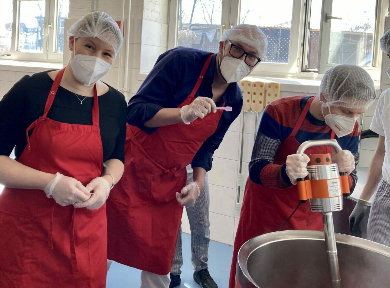 Franziska Giffey, Michael Biel und Kevin Kühnert (von links nach rechts) bei der Marmeladenproduktion.