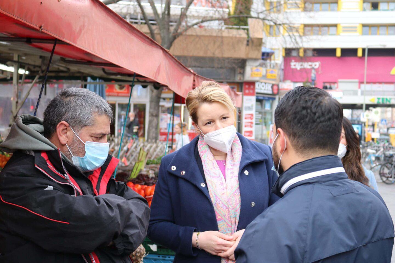 Franziska Giffey (mitte) unterhält sich mit Verkäufern am Kottbusser Tor