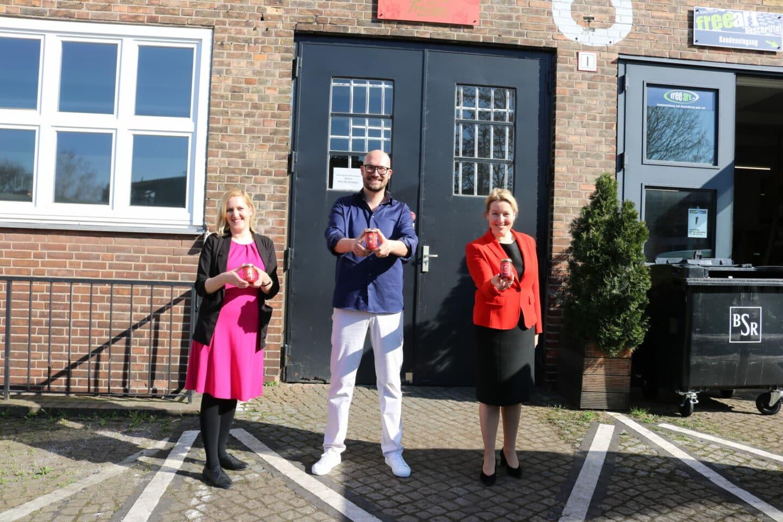 Wiebke Neumann, Michael Biel und Franziska Giffey (von links) halten ein Glas Erdbeermarmelade in ihrer Hand.
